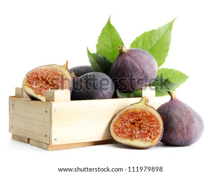 Ripe sweet figs with leaves in wooden crate isolated on white - stock photo