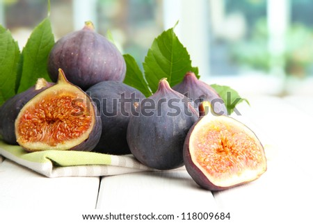 Ripe sweet figs with leaves, on wooden table, on window background - stock photo