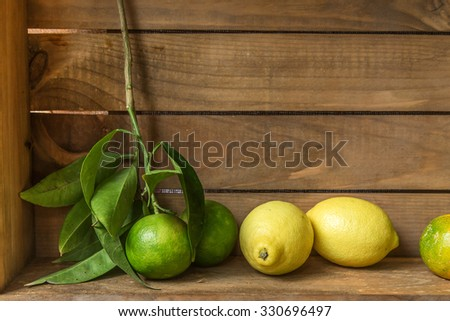 Ripe sweet lemon and tangerine with leaves on old wooden board