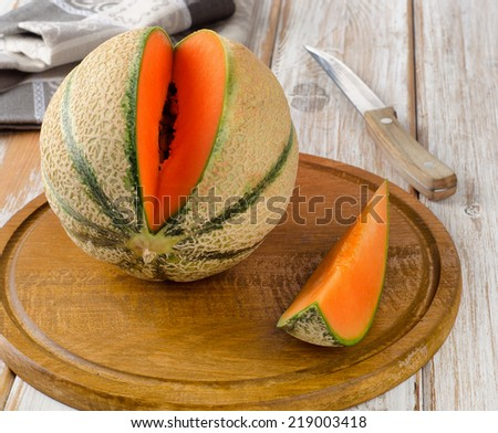 Ripe sweet melon  on the wooden table. Selective focus - stock photo