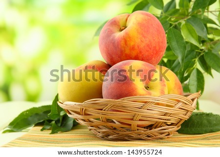 Ripe sweet peaches in basket on table, outdoors