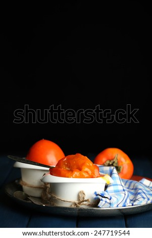 Ripe sweet persimmons, on wooden table - stock photo