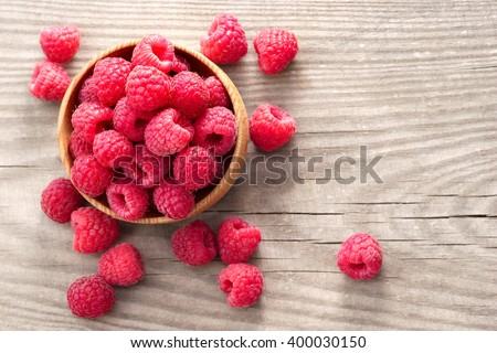 Ripe sweet raspberries in bowl on wooden table. Close up, top view, high resolution product - stock photo