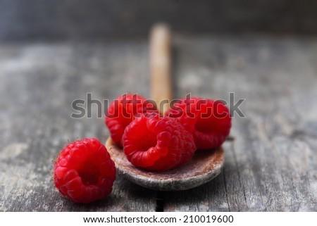 Ripe sweet raspberries in spoon on table - stock photo