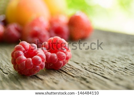Ripe Sweet Raspberries on the Wooden Table Against the Heap of Summer Fruits and Berries - stock photo