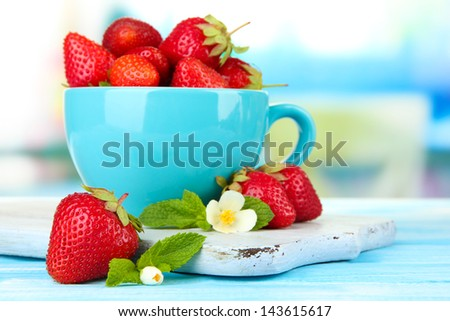 Ripe sweet strawberries in cup on blue wooden table