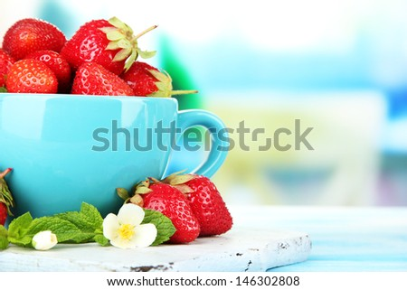 Ripe sweet strawberries in cup on blue wooden table - stock photo