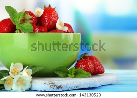 Ripe sweet strawberries in green bowl on blue wooden table