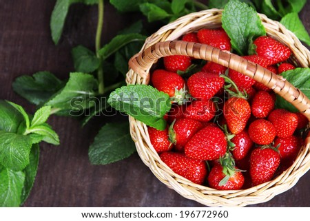 Ripe sweet strawberries in wicker basket and mint leaves on wooden background - stock photo