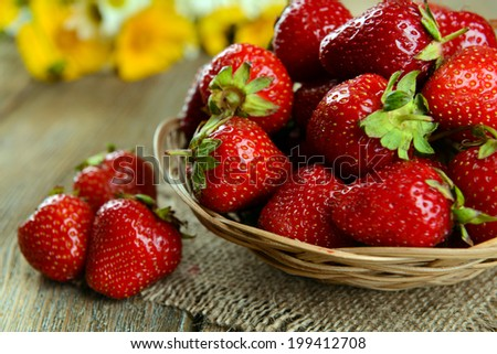 Ripe sweet strawberries in wicker basket on table close-up - stock photo