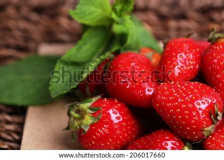 Ripe sweet strawberries  on paper napkin on wicker mat background