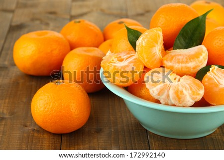 Ripe tangerines in bowl on wooden background