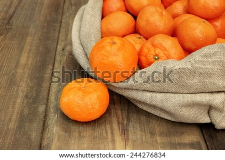 Ripe Tangerines  in Burlap Bag on Grunge Wood Table - stock photo