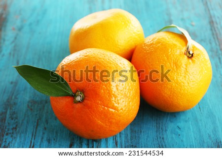 Ripe tangerines with leaves on wooden background - stock photo