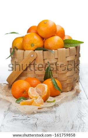 Ripe tasty tangerines with leaves in a basket on a white wooden table - stock photo