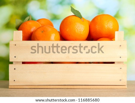 Ripe tasty tangerines with leaves in wooden box on table on green background - stock photo
