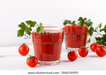 Ripe tomato and juice with parsley on white wooden background