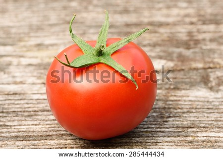 Ripe tomato on a wooden background - stock photo