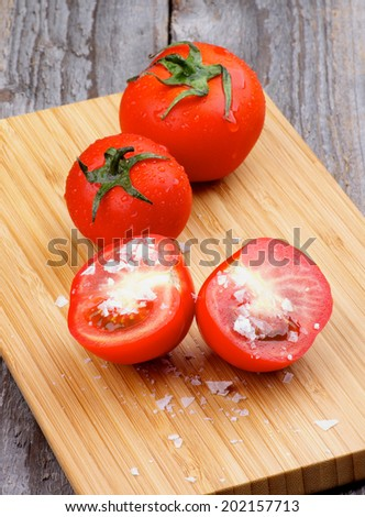 Ripe Tomatoes Full Body and Halves with Salt Flakes on Wooden Cutting Board