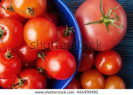 Ripe tomatoes in blue plate over vintage wooden background