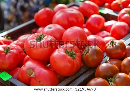 Ripe tomatoes in box on the farmer's seasonal market in europe - stock photo