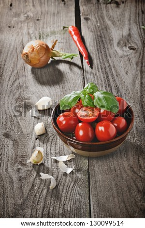 ripe tomatoes in wooden bowl and red hot chili peppers on the wooden desk - stock photo