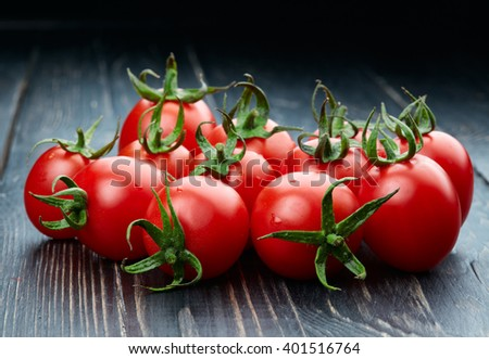 Ripe tomatoes on dark wooden background - stock photo