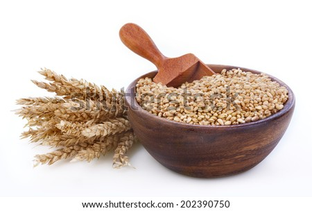 Ripe wheat in a wooden bowl on white background - stock photo