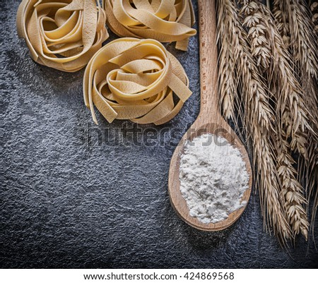 Ripe wheat rye ears wood spoon flour uncooked pasta on black background food and drink concept. - stock photo