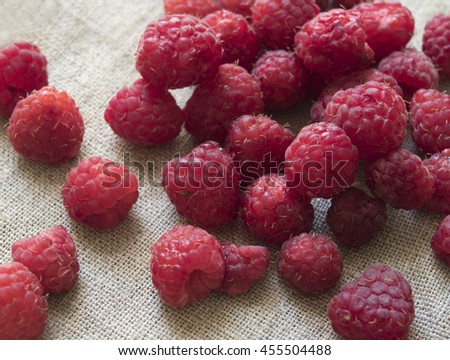 ripe wild raspberries lying on the canvas - stock photo