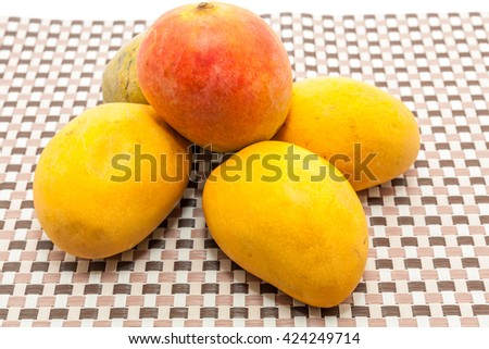 Ripe yellow and red mango fruits on check box background - stock photo