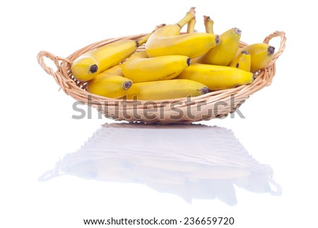 ripe yellow bananas in a wicker basket isolated on white background with reflection - stock photo