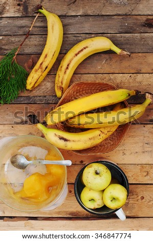 ripe yellow bananas in wicker basket, apples in mug and honey on wooden background, view from above - stock photo