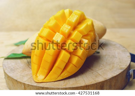 ripe yellow mangoes fruit with green mango leaf in wooden background - stock photo