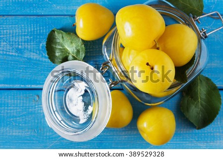 Ripe yellow plums in a glass jar on a blue wooden background. View from above. Bio healthy food background. Organic fruits - stock photo