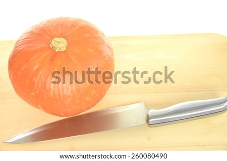Riped orange pumpkin and silver kitchen knife on top of wooden chopping block over white background - stock photo