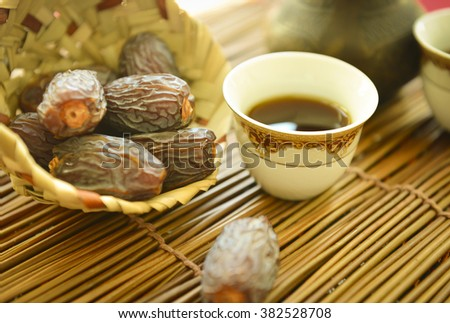 Ripened dates in a small palm basket with Arabic coffee cup. Arabian food. Stock photography. - stock photo