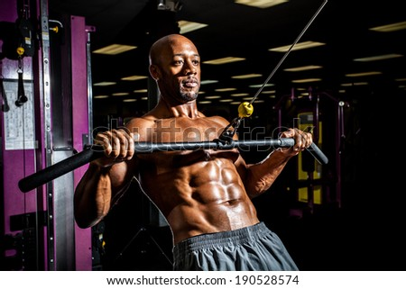 Ripped body builder working out  at the gym. - stock photo