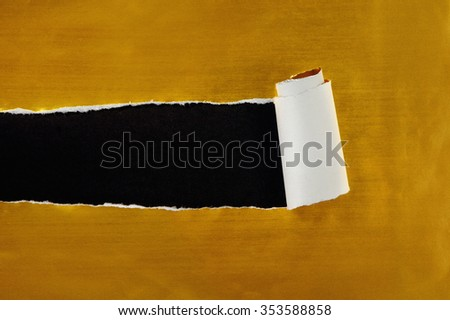 ripped gold paper against a black background - stock photo