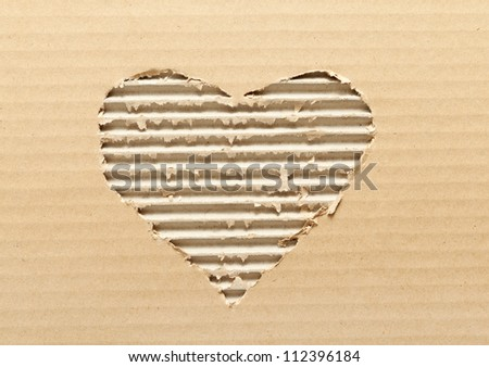 Ripped heart shaped corrugated cardboard, brown background - stock photo