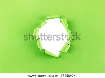 Ripped hole in green paper isolated over a white background - stock photo