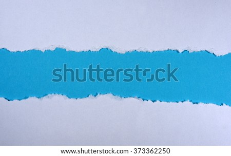 Ripped in white paper on blue background - stock photo