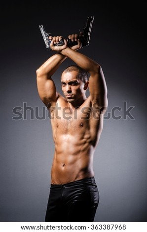 Ripped man with gun against grey background - stock photo