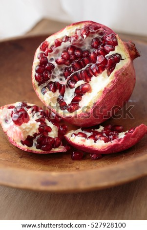 Ripped open fresh ripe pomegranate fruit in a wooden bowl.