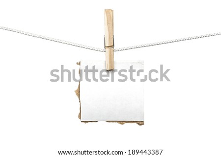 ripped piece of card board hanging on one clothespin, isolated on white.