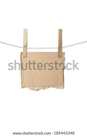 ripped piece of card board hanging on two clothespins, isolated on white.