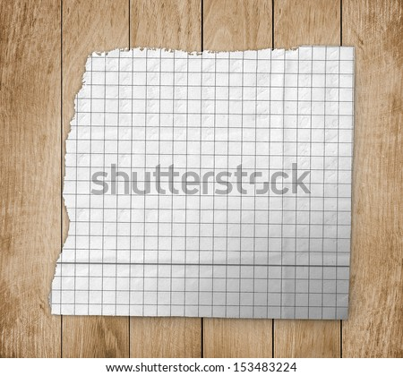 Ripped white paper on wood background - stock photo