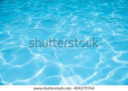Ripple Water in swimming pool witn sun reflection - stock photo
