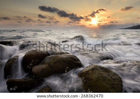 Ripple waves breaking on the rocks at the beach sunset light Focus on rocks foreground. - stock photo