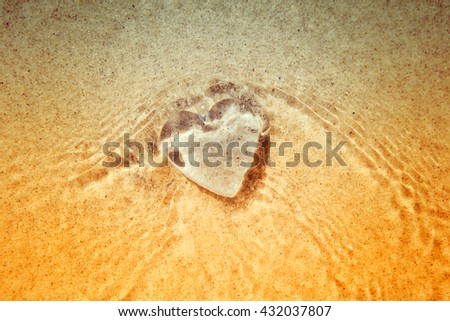 Rippled under water Heart, blurred wave action on beach